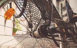 Achterwiel van een fiets met een oranje koplamp Zwarte fietsenrekken in de schaduw van het gebouw op een hete dag stock afbeelding