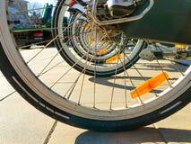 Achterwielen van fietsen bij een huurpost dichtbij een park in de vroege lente in duidelijk weer royalty-vrije stock afbeeldingen
