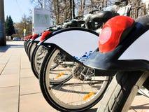 Achterwielen van fietsen bij een huurpost dichtbij een park in de vroege lente in duidelijk weer stock foto