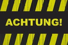 Achtung! auf Deutsch Aufmerksamkeit! Wort geschrieben auf Warnzeichen Lizenzfreie Stockfotografie