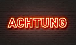 Achtung neon sign on brick wall background. Royalty Free Stock Photos