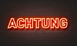 Achtungs-Leuchtreklame auf Backsteinmauerhintergrund Lizenzfreie Stockfotos