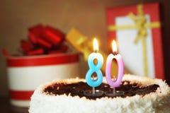 Achtzig Jahre Geburtstag Kuchen mit brennenden Kerzen und Geschenken Lizenzfreie Stockfotos