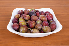 Acid purple and green Plums (Blackthorns)in bowl Stock Images