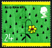 Acid Rain Kills UK Postage Stamp. UNITED KINGDOM - CIRCA 1992: A used postage stamp from the UK, depicting an illustration of a flower dying in the rain stock photo