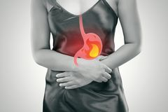 Acid reflux or Heartburn. Acid reflux or Heartburn, The photo of stomach is on the woman`s body against gray Background, Bad health, Female anatomy concept stock image