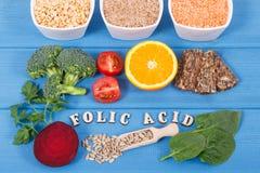 Acide folique d'inscription avec différents ingrédients nutritifs contenant la vitamine B9 et les minerais naturels, concept sain Images stock