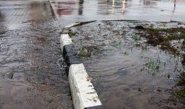 Acidente da fonte de ?gua, ?gua de esgoto De debaixo da quebra no asfalto derramou uma fonte de ?gua da ?gua de esgoto suja desco foto de stock