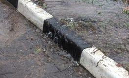 Acidente da fonte de ?gua, ?gua de esgoto De debaixo da quebra no asfalto derramou uma fonte de ?gua da ?gua de esgoto suja desco fotografia de stock