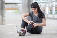 acidente de corrida do pé de ferimento da jovem mulher asiática da aptidão do exercício que exercita na rua na cidade urbana asse imagem de stock royalty free