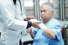Acidente paciente asiático da mulher superior ou idosa da senhora idosa no braço com a atadura na cadeira de rodas na divisão de  imagem de stock royalty free