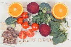 Acido folico dell'iscrizione con i prodotti nutrienti che contengono vitamina B9 e fibra dietetica, concetto sano di nutrizione immagini stock libere da diritti