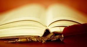 Acient-offenes Buch auf dem Tisch und ein Stift Stockfoto