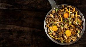 Acier de poêle avec des champignons et des jaunes d'oeuf mous Image stock
