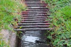 Acier sur la grille en métal de drain ou de fossé de l'eau au foyer choisi d'herbe de plancher avec la profondeur du champ image stock