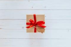 Acima da caixa de presente marrom com a etiqueta no fundo da placa de madeira Presente b Imagens de Stock Royalty Free