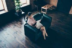Acima da opinião de ângulo alto perito experiente especializado da senhora segura elegante atrativa agradável que senta-se no sof fotografia de stock