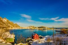 Acima da vista de algumas construções de madeira na baía com os barcos na costa nas ilhas de Lofoten cercadas com nevado Imagem de Stock