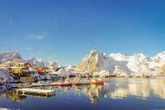 Acima da vista de algumas construções de madeira na baía com os barcos na costa nas ilhas de Lofoten cercadas com nevado Foto de Stock