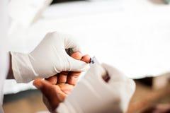 Acima da vista do dedo do sangramento após a punctura para o teste livre do hiv no hospital africano foto de stock