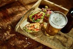 Acima da vista em tapas camarão e em petisco do vegetal com cerveja foto de stock
