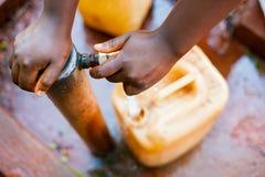 Acima da vista próxima acima do tanque de enchimento da mão africana nova da criança com água da torneira com fundo verde imagem de stock royalty free