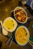 Acima de uma vista de três placas com alimento, macarronetes, galinha e sopa sobre uma tabela de madeira dentro de um restaurante Imagem de Stock