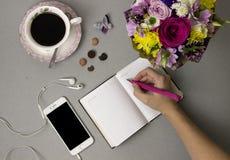 Acima do café, um ramalhete das flores, um caderno, fotografia de stock