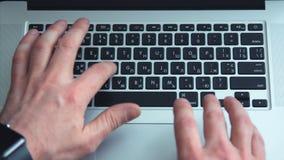 Acima do tiro do homem que usa o laptop no fundo da tabela do escritório Homem que datilografa no teclado do portátil Vista super video estoque