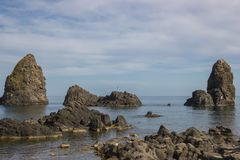 Acitrezza Sicilien sikt av den cyclopean ön framme av kusten, härlig solig seascape royaltyfri foto