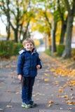 Acitve-Kinderjunge, der in Herbstpark geht Stockbild