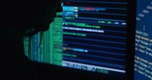 Acker в коде клобука треская используя компьтер-книжку и компьютеры от его темной комнаты хакера