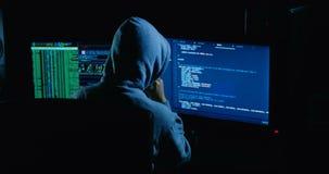 Acker w kapiszonu łupania kodzie używać laptop i komputery od jego ciemnego hackera pokoju zbiory wideo