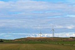 Ackerland mit Ansicht der enormen Windkraftanlagewindmühle im Hintergrund, Stockfotografie