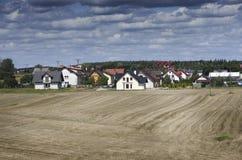 Ackerland mit Dorf auf Hintergrund Lizenzfreie Stockfotografie