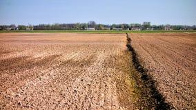 Ackerland mit Dorf im Hintergrund Stockbild