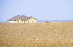 Ackerland mit einem gelben Haus Stockbilder