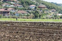 Ackerland mit Gebäuden auf Hügel, Albanien Stockbild