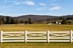 Ackerland mit weißem Zaun-Vordergrund Lizenzfreie Stockfotos