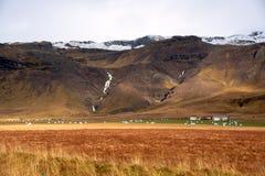 Ackerland punktiert mit eingewickeltem Hay Bales an der Unterseite von majestätischen Bergen stockbild