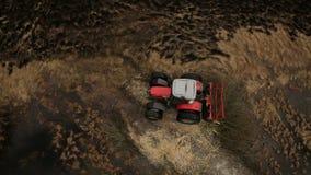 Ackerlandvogelperspektive mit einem Traktor, der Boden pflügt stock footage