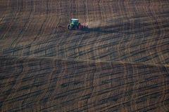 Ackerschlepper behandelt Erde auf Feld Stockbilder