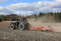 Ackerschlepper und Landwirt auf Feld am Frühling Lizenzfreies Stockfoto