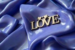 Ackground av lilor, blått skinande tyg, med inskriftförälskelsen Royaltyfri Fotografi
