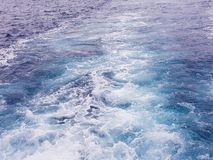 Ackground water surface behind of fast moving motor boat. Vacation holiday concept background. Blue, trip, summer, ocean, speed, travel, sea, wave, ship, foam royalty free stock images