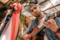 Ackord för håll för fundersam manlig gitarrist försökande nytt royaltyfria bilder