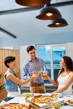 aclamaciones Amigos felices que animan las botellas de cerveza dentro Partido cele imágenes de archivo libres de regalías
