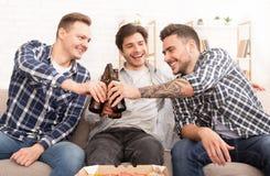 aclamaciones Amigos felices que beben la cerveza en casa foto de archivo libre de regalías