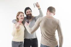 aclamaciones Amigos que beben el alcohol Los mejores amigos celebran con las bebidas alcohólicas La mujer y los hombres bonitos g fotografía de archivo libre de regalías