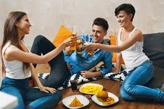 aclamaciones Gente que tuesta la cerveza, comiendo los alimentos de preparación rápida Amigos Celebra imágenes de archivo libres de regalías